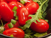 Cherry tomatoes in the salad with greens. macro — Stock Photo