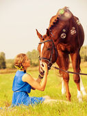 Young nice girl with horse in the meadow — Stock Photo
