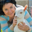 Girl with baby goat. focus at goat — Stock Photo