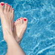 Stock Photo: Females feet over the water
