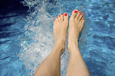 Females feet splashing in the water — Stock Photo