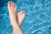 Females feet over the water — Stock Photo