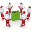 Stock Photo: Santas around green packet.