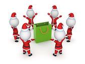 Santas around green packet. — Stock Photo