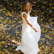 Happy bride in white dress in autumn defoliation - Stock Photo