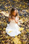 Pretty bride in white dress in sunny autumn park — Stock Photo