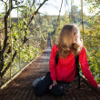 Foto de Stock  : Womhiking resting on suspension bridge