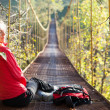 Woman hiking sitting in suspension bridge and resting - Stock Photo