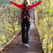 Woman hiking in suspension bridge with outstretched to hands - Stock Photo