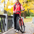Womcyclist with bike in autumn park — Stock Photo #13962265
