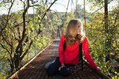 Woman hiking resting on the suspension bridge — Stok fotoğraf
