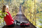 Woman hiking sitting in suspension bridge and resting — Stock Photo