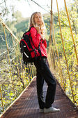 Young woman hiking in suspension bridge — Stok fotoğraf