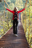 Woman hiking in suspension bridge with outstretched to hands — Stock Photo