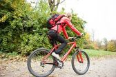 Woman cyclist riding a bike in autumn park — Stock Photo