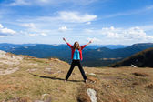 Tourist stretching out her arms while stands on peak of mountain — Stock Photo