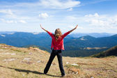 Hiker woman on a peak mountain with raised hands — ストック写真