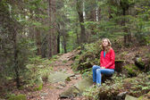 Hiker woman sitting on a halt in stones among the forest — Stock Photo