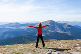 Hiker standing on a peak over the mountain with raised hands — Stock Photo