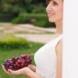 Smiling greek woman with grapes in her hands in the summer park - Stock Photo