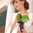 Portrait of greek woman with bunch of grapes in her hands - Stock Photo