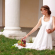 Greek bride sitting against the background of a classical colon - Stock Photo