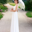 Beautiful laughing bride in white dress with decorative umbrella - Stock Photo