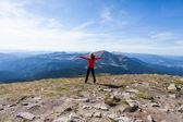 Hiker woman standing on mountain edge and looking to a sky — Stock Photo