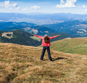 Woman tourist on the mountain with raised hands feeling success — Stock Photo