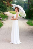 Beautiful laughing bride in white dress with decorative umbrella — Stock Photo