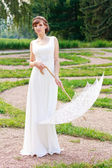 Elegant woman in white dress with decorative umbrella in a vinta — Stock Photo