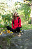 Young woman backpacker enjoying relaxation in the autumn forest — Stock Photo