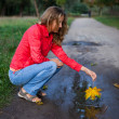 Young woman playing an maple leaf in puddle. Autumn outdoor - Stock Photo