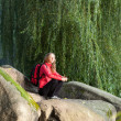Hiker woman sitting on a halt in rocks among the green nature - Stock Photo