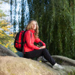 Woman backpacker enjoying relaxation on a halt in rocks - Stock Photo