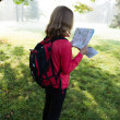 Young backpacker read the map among the sunny nature - Stock Photo