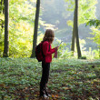 Young hiker read the map in the sunny green forest - Stock Photo