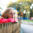 Young woman relaxation leaning on a wooden fence - Stock Photo