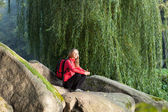 Hiker woman sitting on a halt in rocks among the green nature — Stock Photo