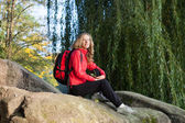 Woman backpacker enjoying relaxation on a halt in rocks — Stock Photo