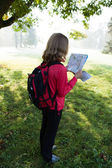 Young backpacker read the map among the sunny nature — Stock Photo
