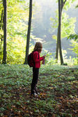Young hiker read the map in the sunny green forest — Stock Photo