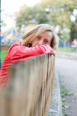Young woman relaxation leaning on a fence and put head on hands — Stock Photo