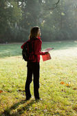 Young hiker with map in hands in the morning sun rays — Stock Photo