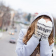 Woman in winter clothes covered her face with wool mittens — Stock Photo