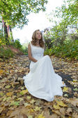 Young bride in white dress on autumn nature — Stock Photo