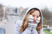 Frozen young woman heated by wool mittens and a from hood — Stockfoto