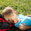 Girl backpacker enjoying relaxation lying in the fresh grass — Stock Photo
