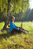 Young cyclist enjoying relaxation in spring in the morning park — ストック写真