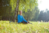 Woman cyclist relaxing in spring park — Stock Photo